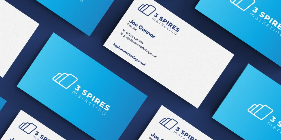 Business cards laying flat on a blue table