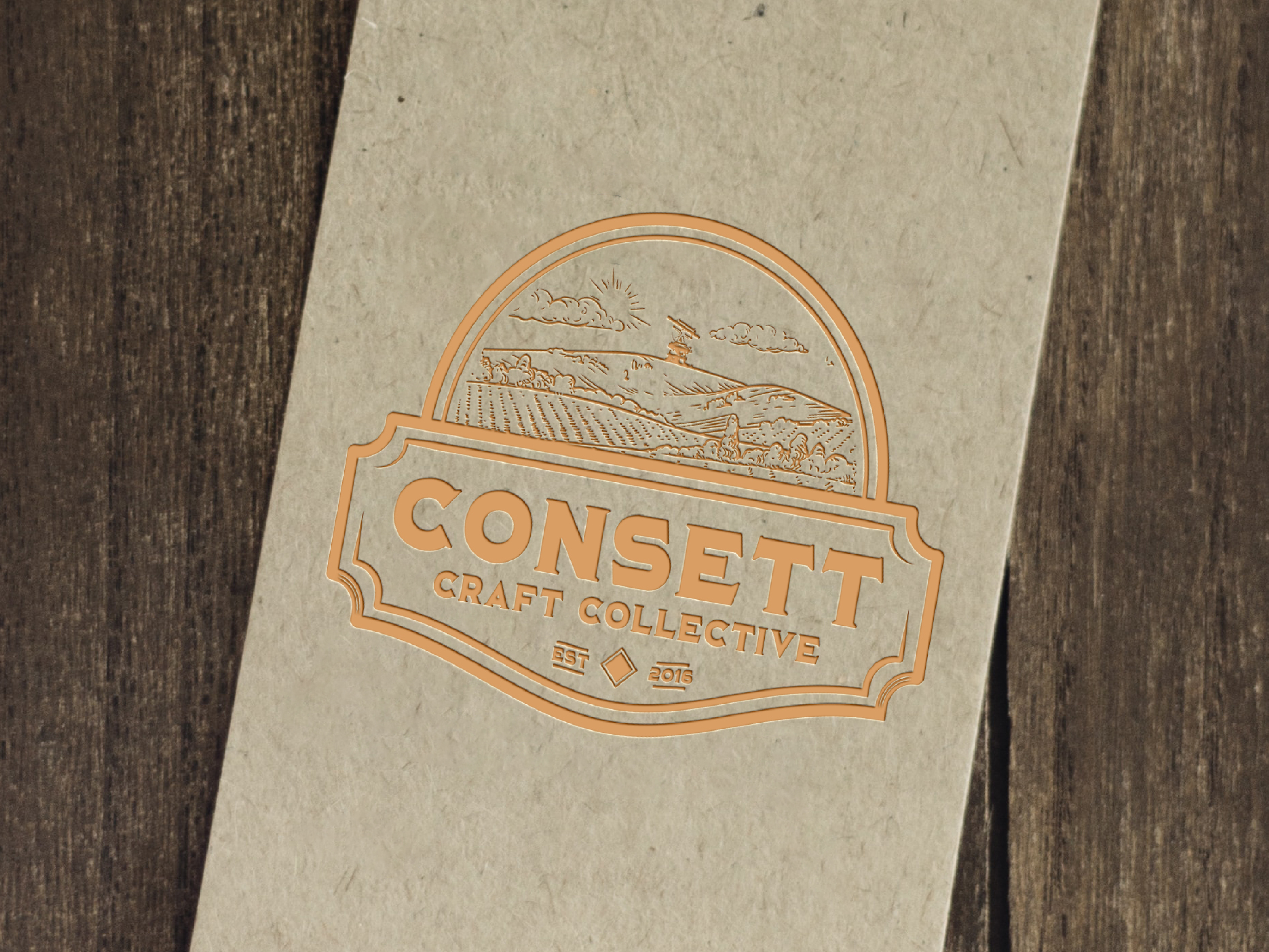 A mocked up logo embossed on recycled card. On Top of a wooden surface