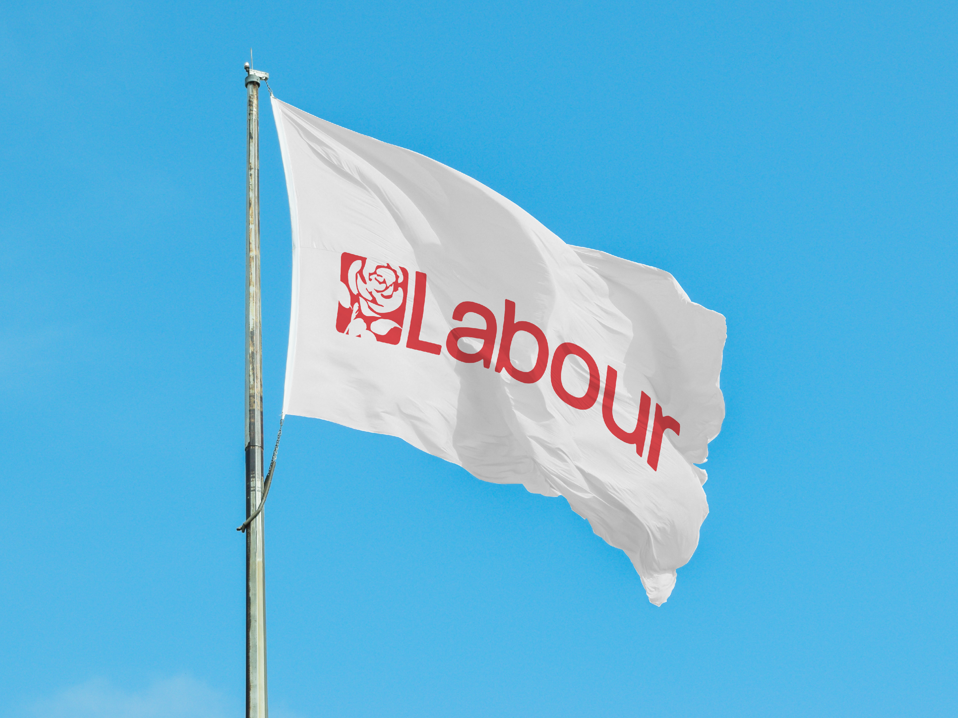 Labour Party flag waving in the wind, infront of a bright blue sky